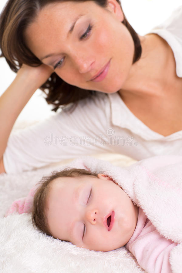 Baby girl sleeping with mother care near. On white fur stock photo