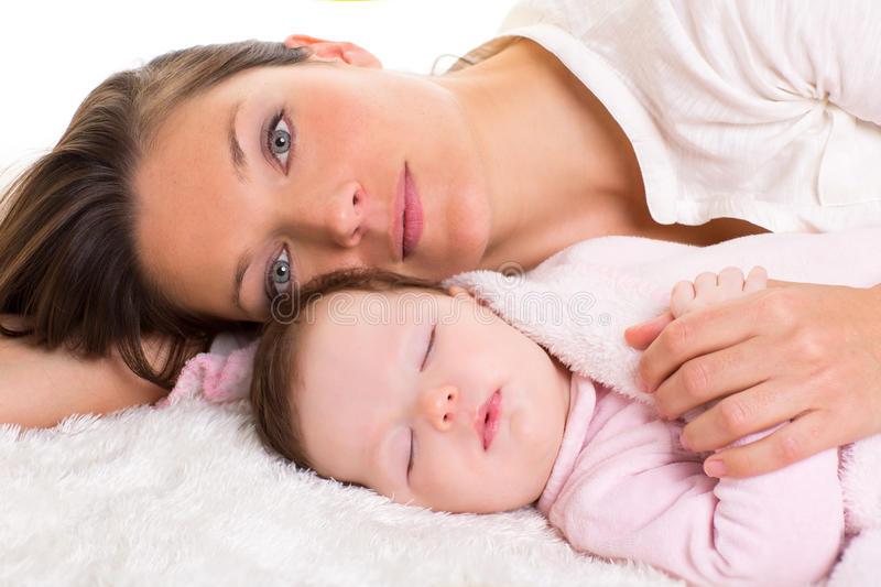 Baby girl sleeping with mother care near. On white fur royalty free stock photos