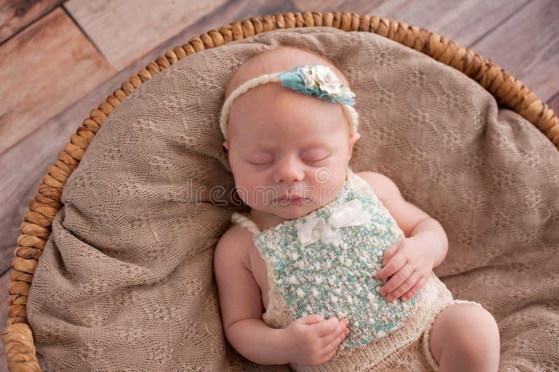 Baby Girl Sleeping in a Wicker Basket stock photo