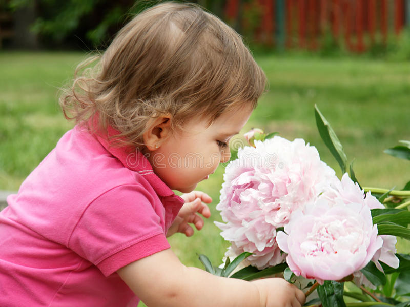 Baby girl smelling peony flowers