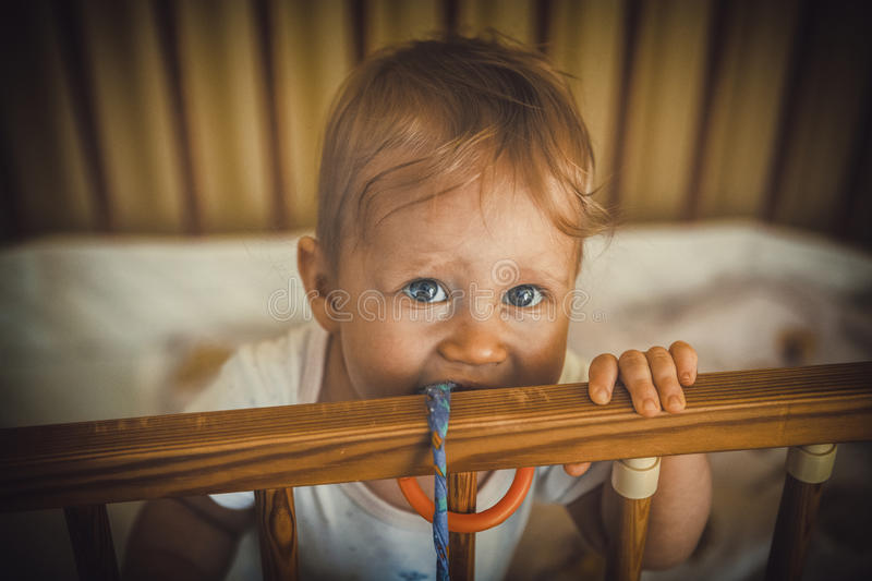 Baby girl is smiling in the crib and holds onto the side of the. Bed stock images