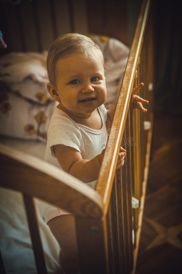 Baby girl is smiling in the crib and holds onto the side of the. Bed stock image