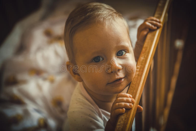 Baby girl is smiling in the crib and holds onto the side of the. Bed royalty free stock photo