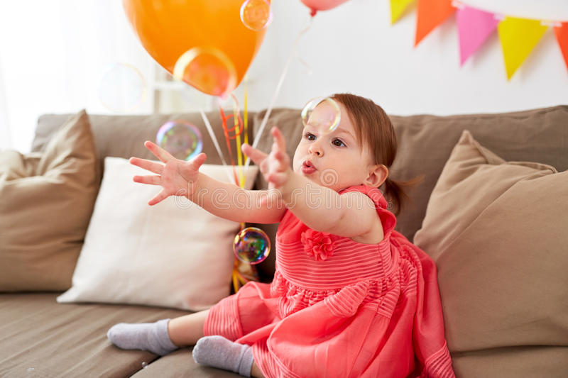 Baby girl with soap bubbles on birthday party. Childhood, holidays and people concept - happy baby girl playing with soap bubbles on birthday party at home royalty free stock images