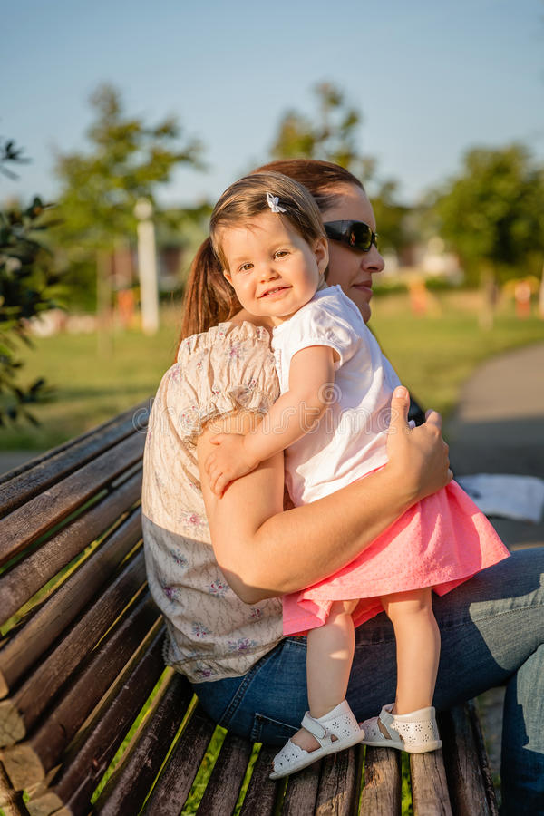 Baby girl standing on a bench hugging to woman. Portrait of happy baby girl standing on park bench hugging to a women with sunglasses royalty free stock photos
