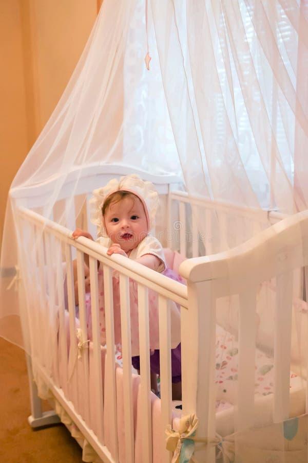 Baby girl standing in her crib. stock photo