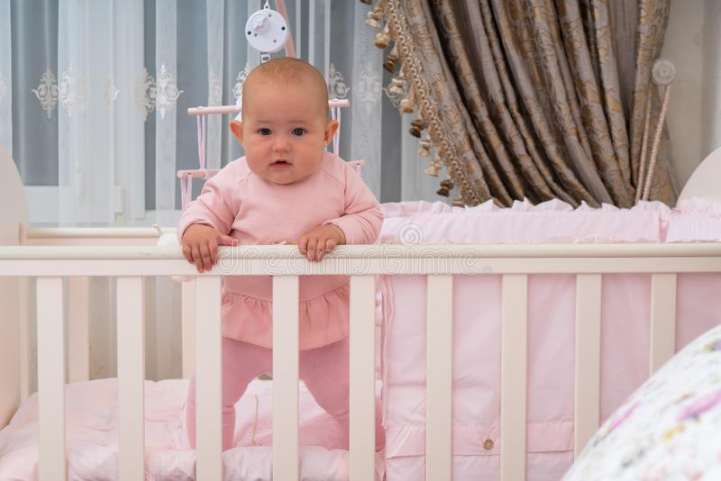 A baby girl standing in crib in pink bedroom scene. royalty free stock photography
