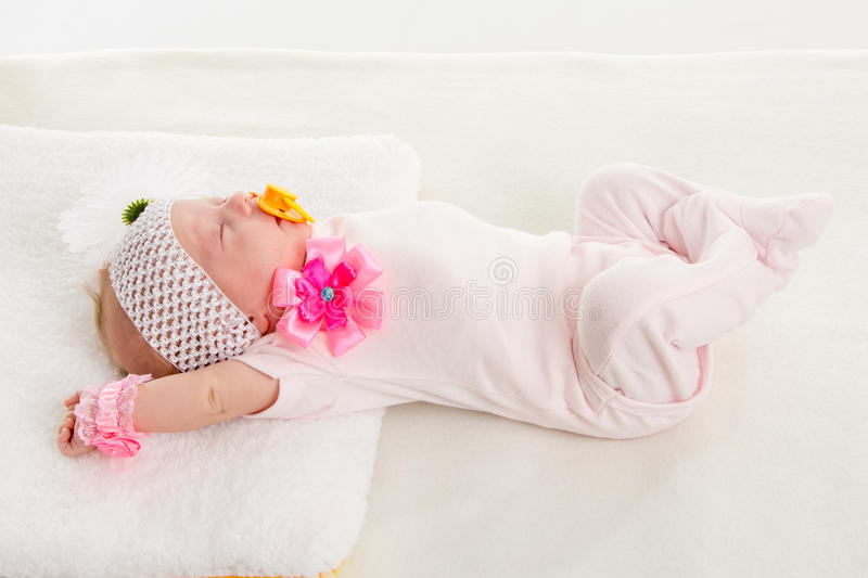 Baby girl stretches in his sleep lying in bed. A two-month baby girl Europeans on the back with a bandage on his head with a flower lying on a soft bed royalty free stock images