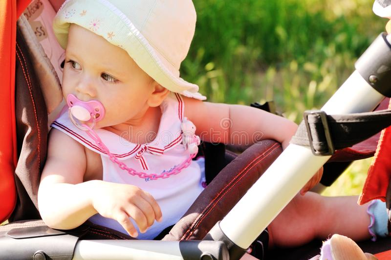 Baby girl in   stroller royalty free stock photos