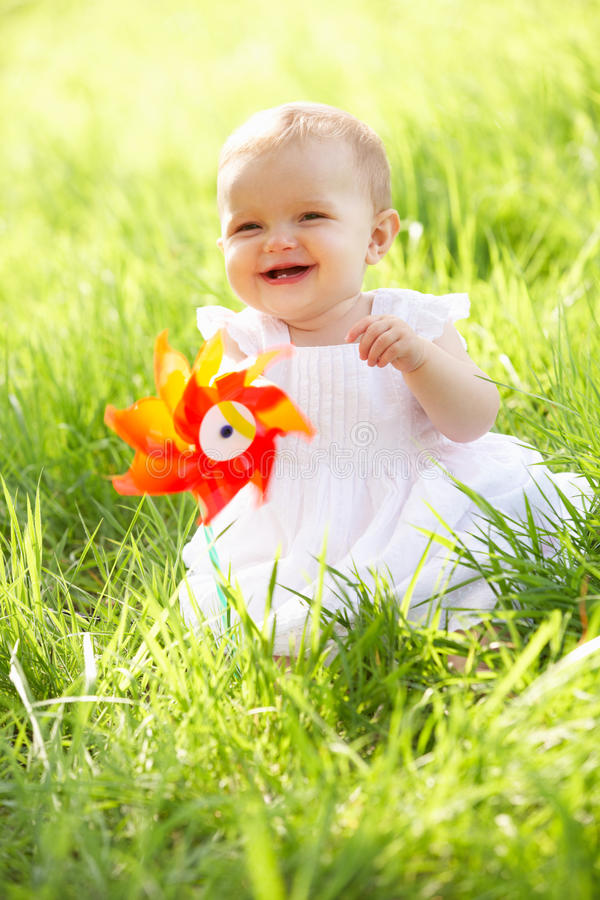 Baby Girl In Summer Dress Sitting In Field. Holding Windmill royalty free stock image