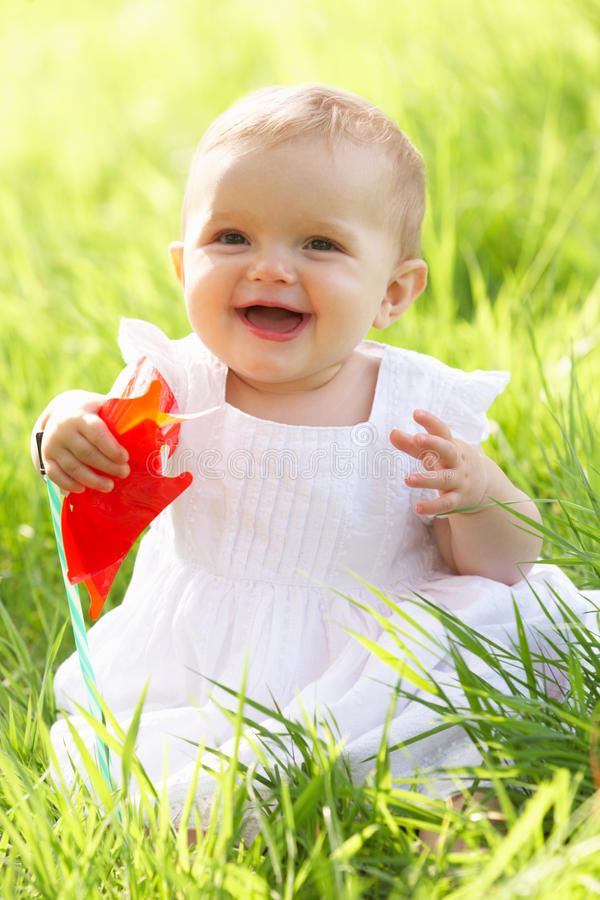 Baby Girl In Summer Dress Sitting In Field. Holding Windmill stock photos