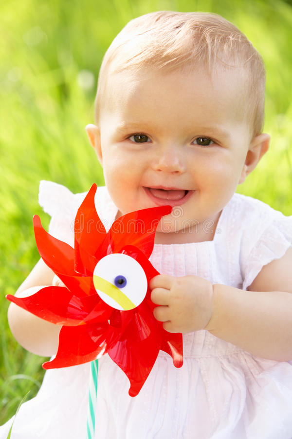 Baby Girl In Summer Dress Sitting In Field. Holding Windmill royalty free stock photo