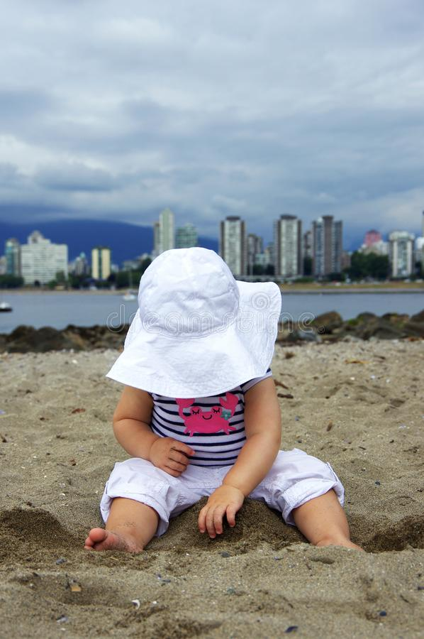 Baby girl in summer outfit and sunhat, touching sand at beach in Vancouver, BC, Canada. stock photography