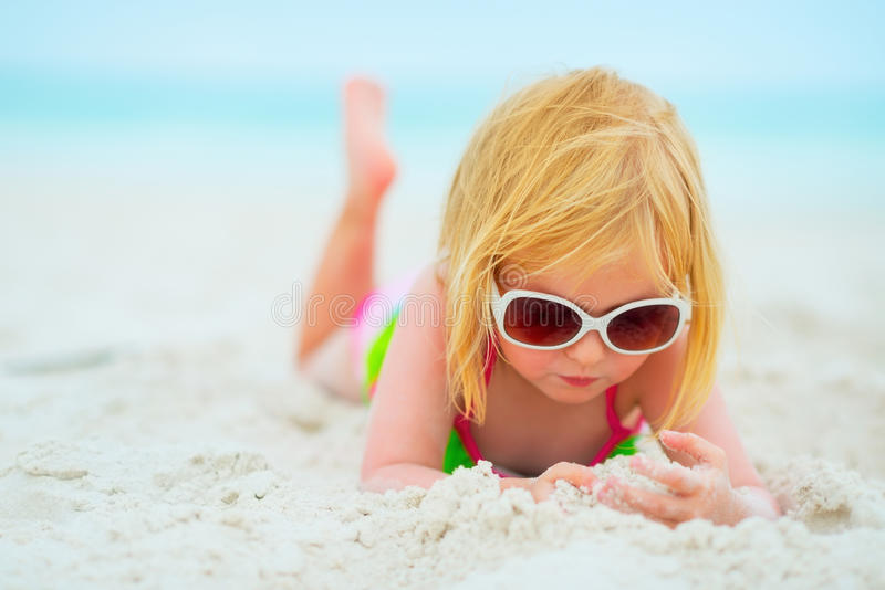 Baby girl in sunglasses laying on beach. Baby girl in sunglasses laying on sandy beach stock image