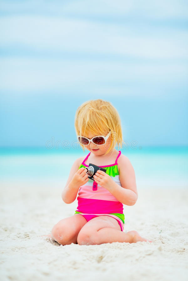 Baby girl in sunglasses with photo camera. Sitting on beach royalty free stock photos