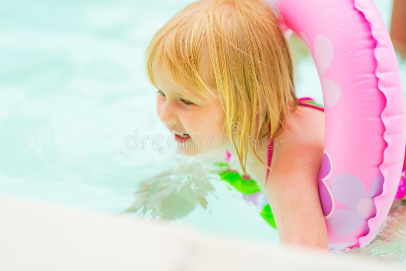 Baby girl with swim ring swimming in pool. Happy baby girl with swim ring swimming in pool stock photo