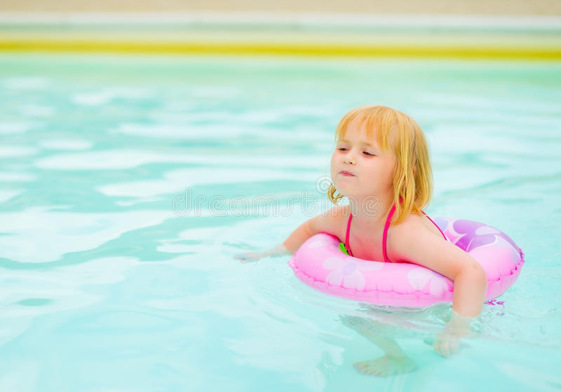 Baby girl with swim ring in swimming pool. Baby girl in swimsuit with swim ring in swimming pool stock images