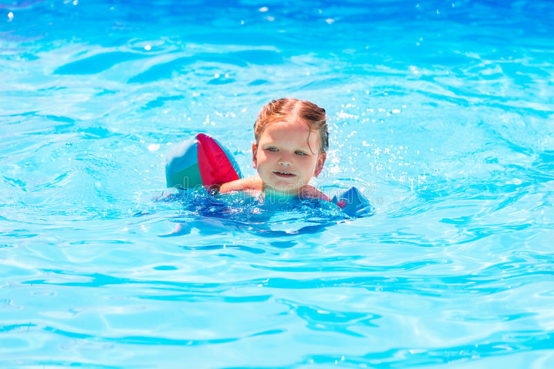 Baby girl swimming in pool with floats sleeves. Baby girl swimming in blue pool with floats sleeves at summer vacation stock photo