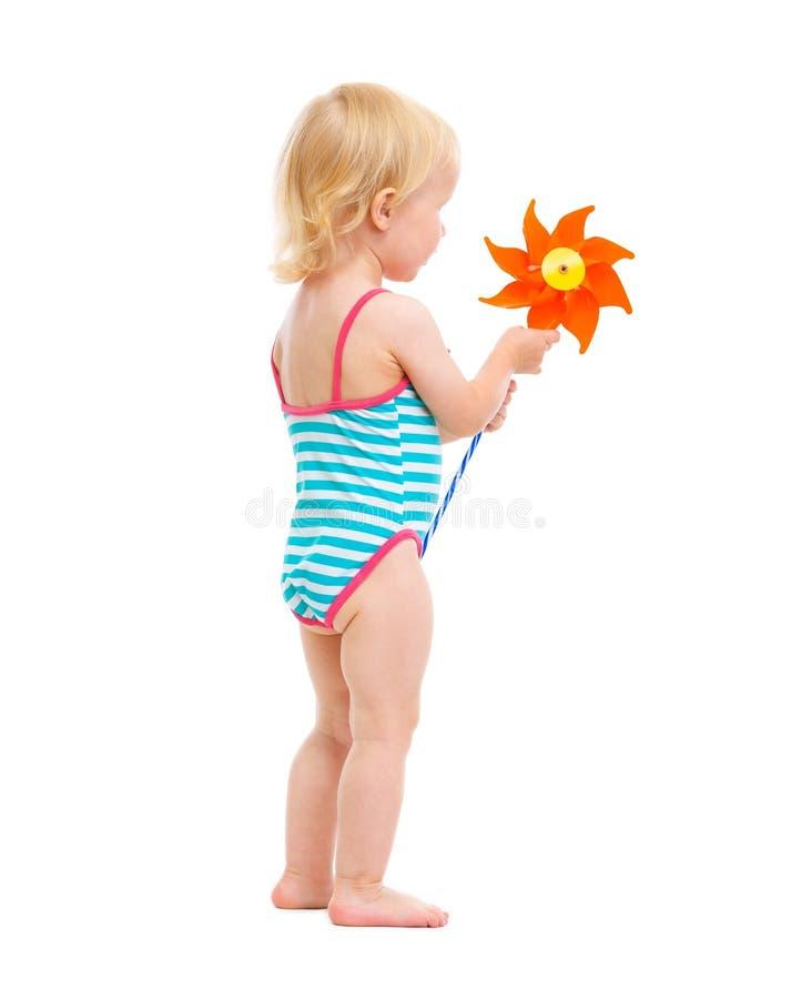 Baby girl in swimsuit holding pinwheel. Isolated on white stock photos