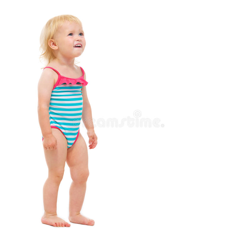 Baby girl in swimsuit looking on copy space. Isolated on white royalty free stock photography