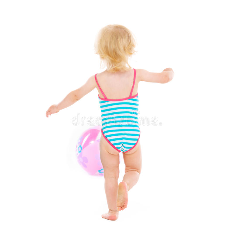 Baby girl in swimsuit playing with ball. Rear view. Baby girl in swimsuit playing with ball isolated on white. Rear view royalty free stock photography