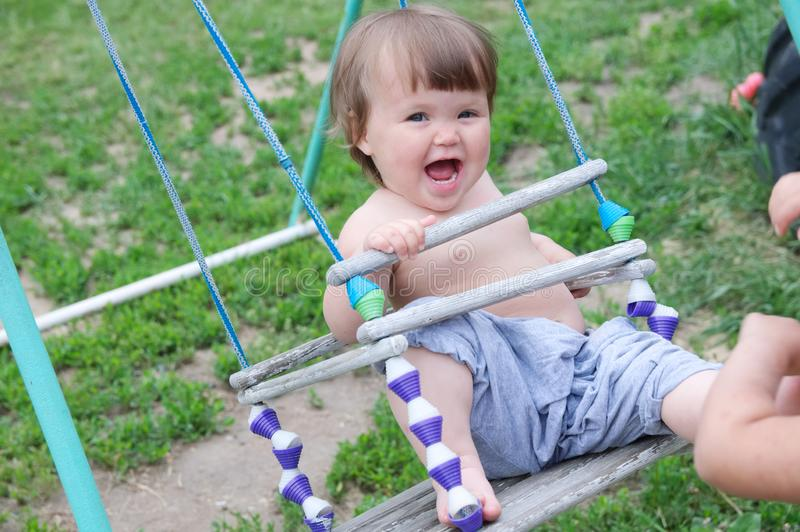 Baby girl swing at summer, happy smiling child. Domestic lifestyle. Emotionally laughing kid royalty free stock photos