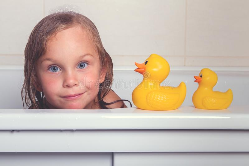 Baby girl taking bath with foam and toys royalty free stock image