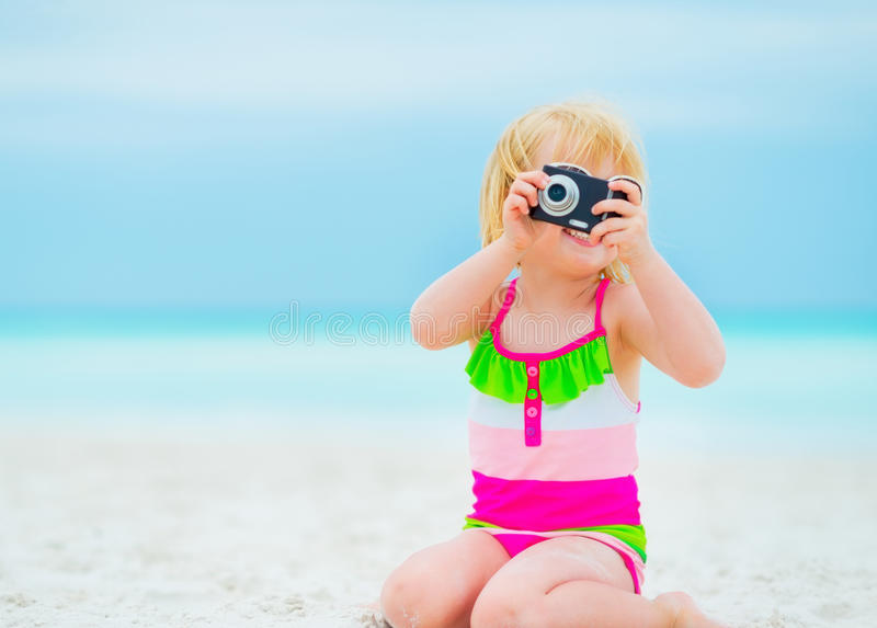 Baby girl taking photo on beach. Baby girl in swimsuit taking photo on beach stock photography