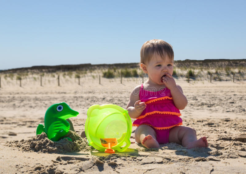 Baby girl tasting sand on beach stock image
