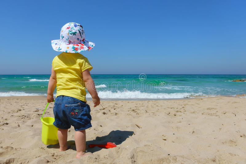 Baby girl toddler with bucket and spade on the beach stock photo