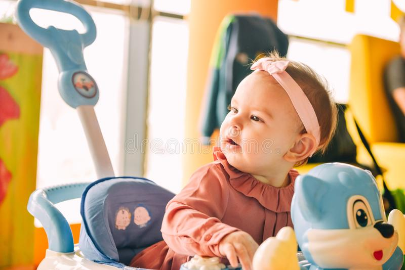Baby girl toddler learning to walk in a walker with pink headband. Baby girl toddler learning to walk in a walker with pink royalty free stock photography