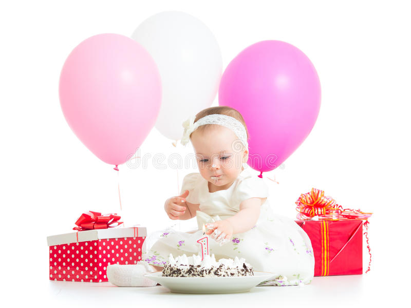 Baby girl touching light on birthday cake royalty free stock images