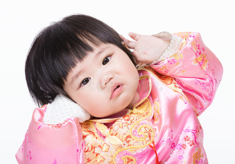 Baby girl with traditional chinese clothing and having funny posture royalty free stock image