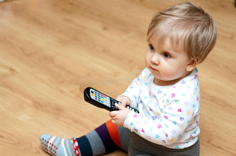 Baby girl with TV remote stock photography