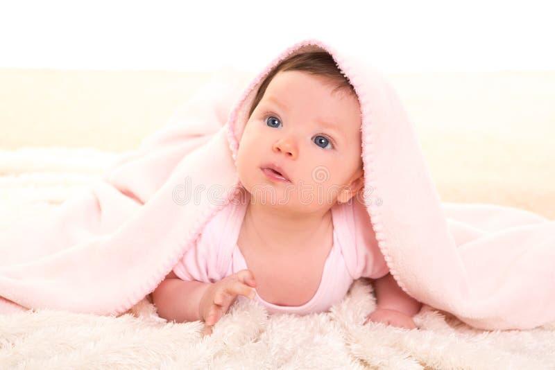 Baby girl under hidden pink blanket on white fur stock image