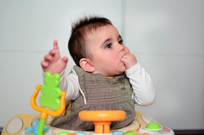 Baby girl in a walker. Cute baby girl with hand in the mouth playing in her walker stock photo
