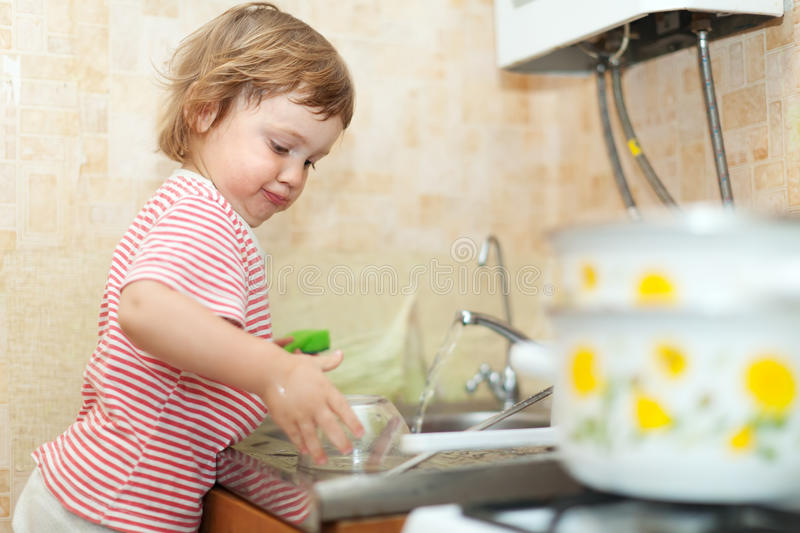 Baby girl  washes dishes