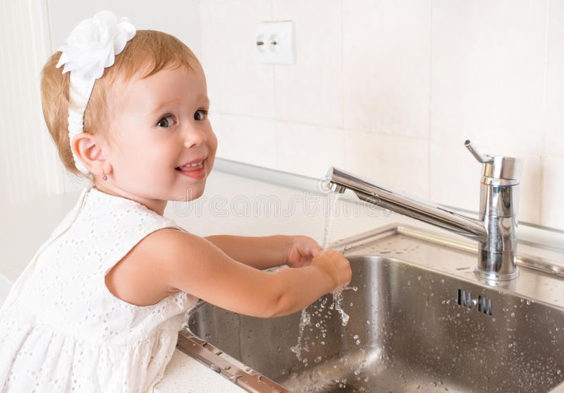 Baby girl washes her hands in the bathroom. With running water royalty free stock photos