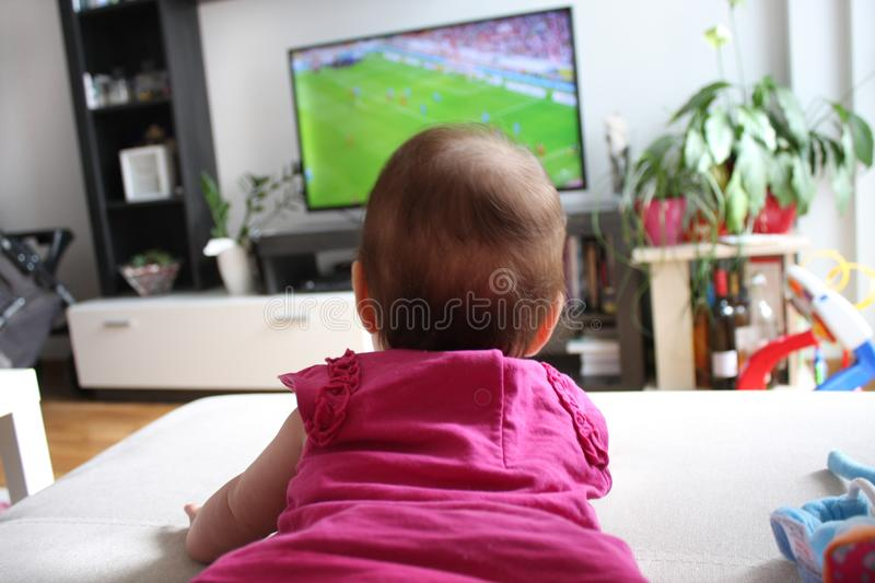 Baby girl watching a soccer on TV.  royalty free stock image