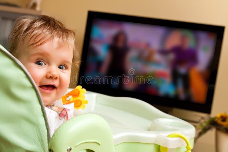Baby girl watching tv stock photos