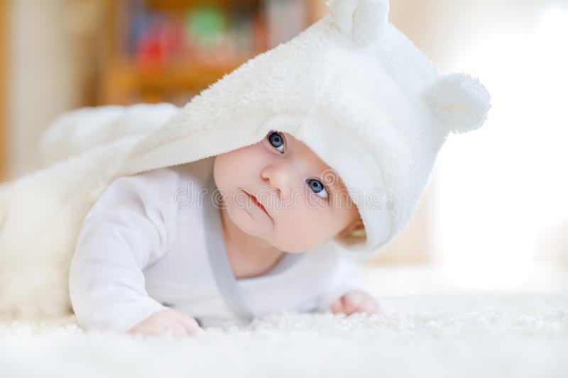 Baby girl wearing white towel or winter overal in white sunny bedroom. Baby girl with blue eyes wearing white towel or winter overal in white sunny bedroom stock image
