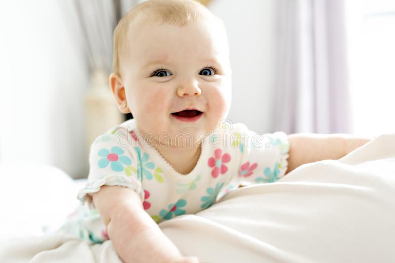 Baby girl in white bedding at home look nice royalty free stock images