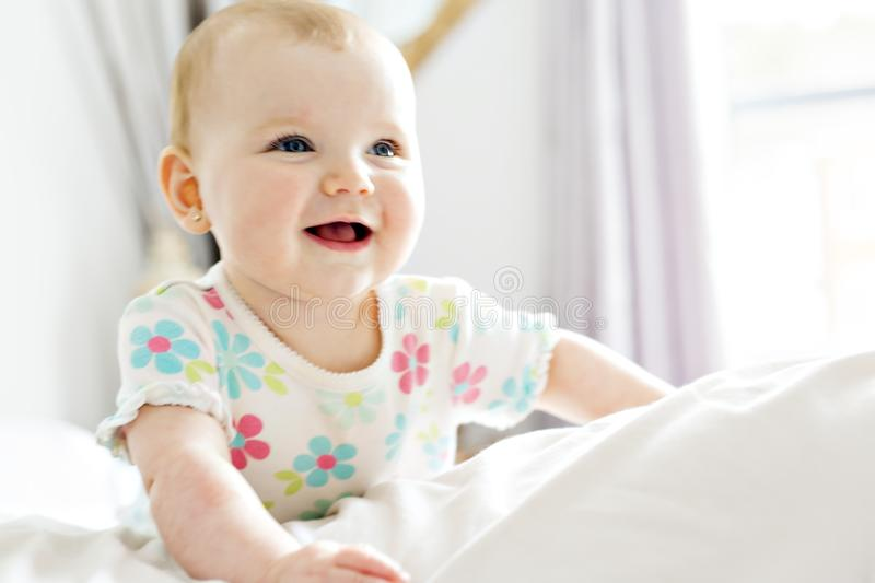 Baby girl in white bedding at home look nice royalty free stock photography