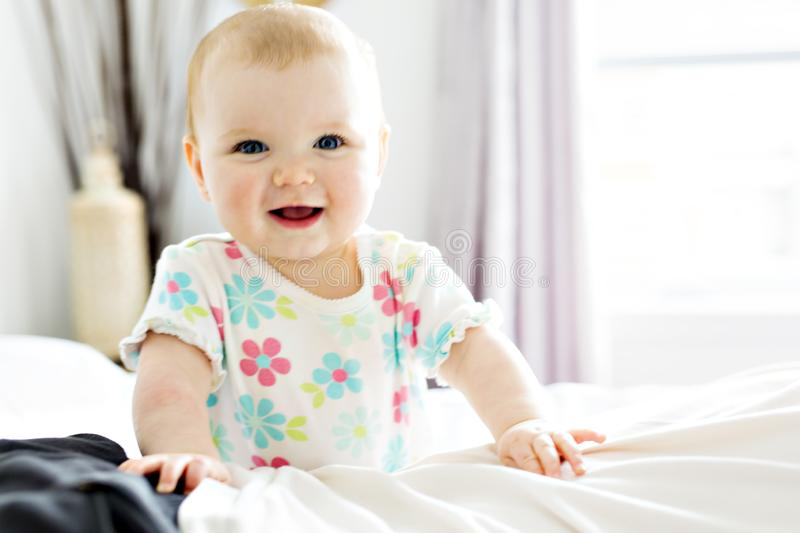 Baby girl in white bedding at home look nice stock image
