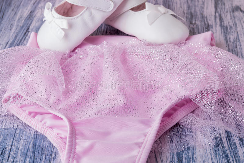 Baby girl white dancing shoes near leotards stock photography
