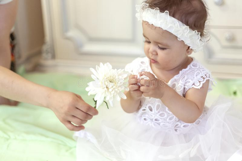 Baby girl in white dress taking a beautiful single white flower. Little princess playing with a white flower at her first birthday royalty free stock images