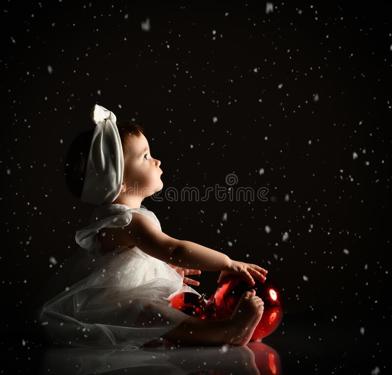 Baby girl in white headband and dress, barefoot. Holding two red balls, looking up, sitting on floor. Twilight, black background. royalty free stock photo