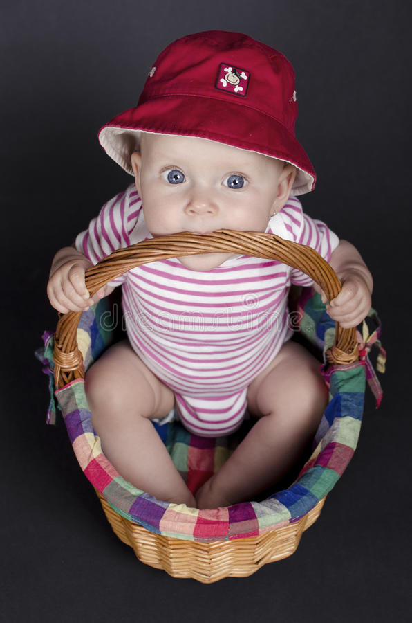 Baby Girl in a Wicker Basket royalty free stock photography