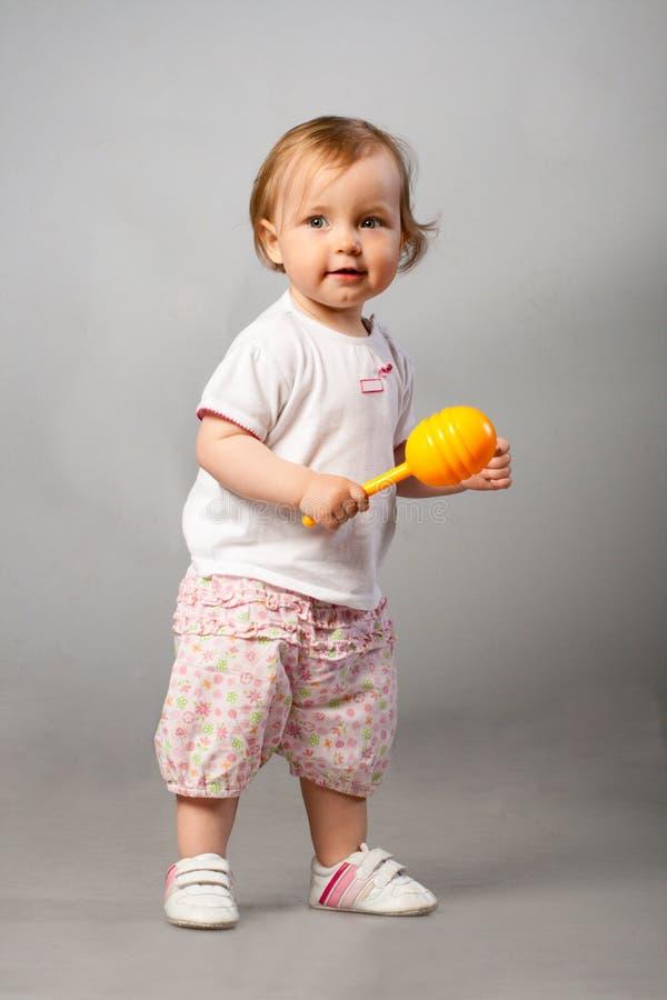 Free Baby Girl With Orange Maraca. Royalty Free Stock Photos - 9643958