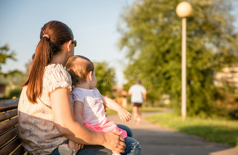 Baby girl and woman sitting on a park bench. Baby girl and women with pigtail sitting on a park bench looking at men runner stock images